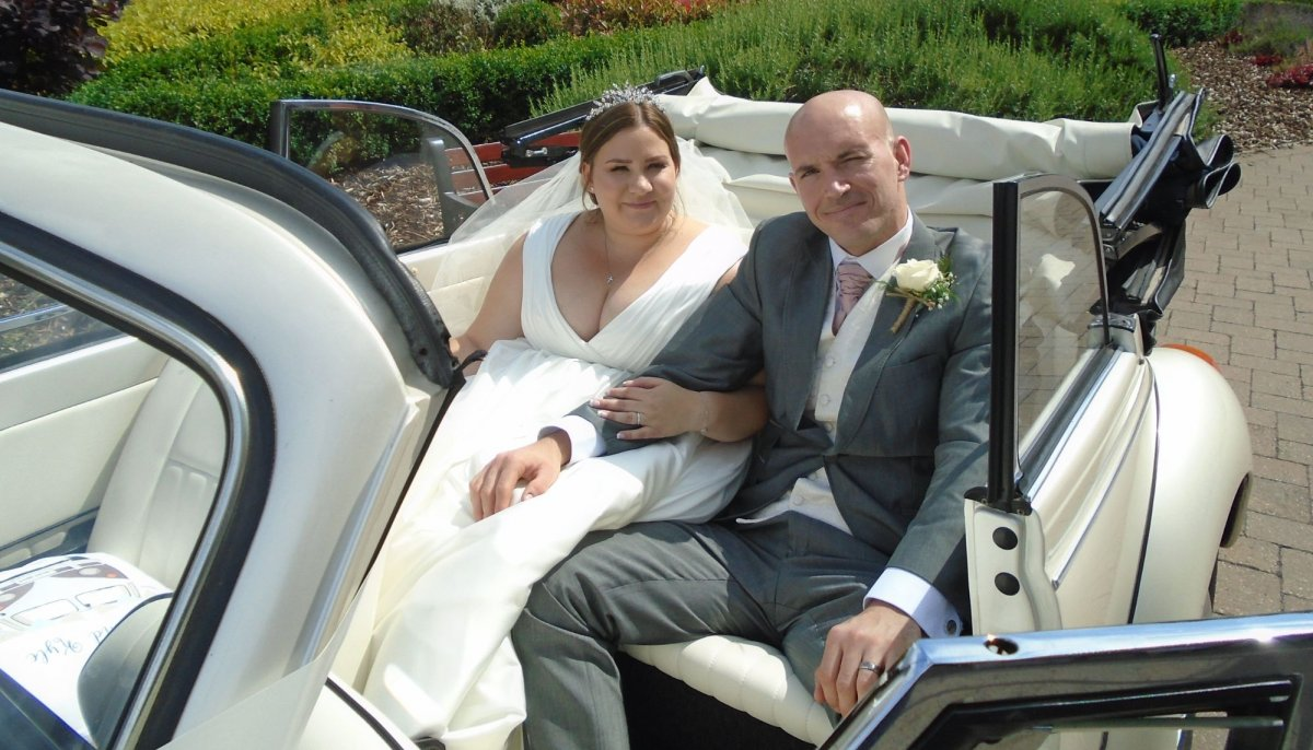 Close up of Bride and Groom holding hands sat in the back of an ivory vintage VW Beetle cabriolet wedding car with roof down,