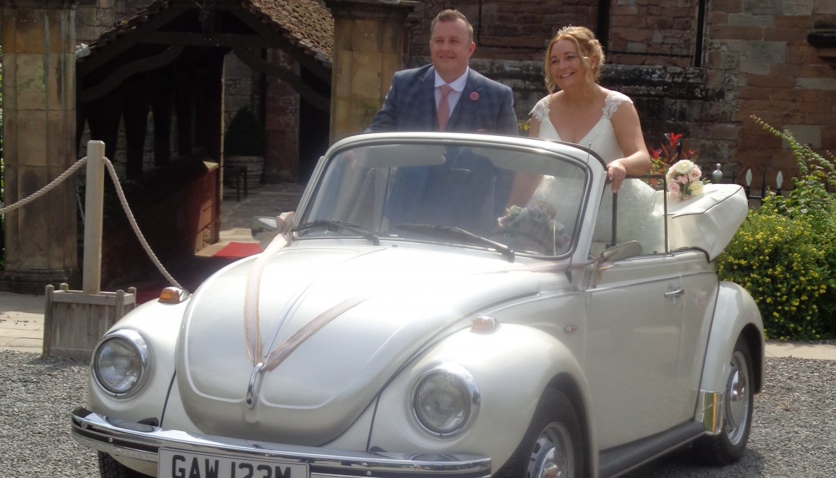 Bride and Groom stood up in the back of an ivory vintage VW Beetle cabriolet wedding car with roof down outside New Hall hotel