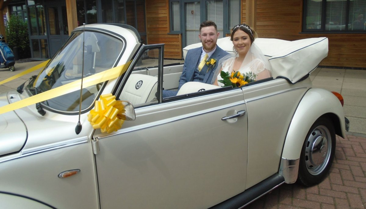 Bride and Groom smiling sat in the back of an ivory vintage VW Beetle cabriolet wedding car with roof down, bride is holding a sunflower bouquet
