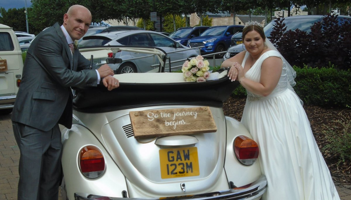 Rear photo of Bride and Groom leaning of an ivory vintage VW Beetle cabriolet wedding car with roof down and a wooden sign on it's boot saying So the journey begins