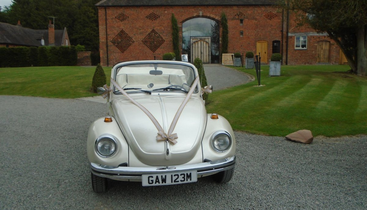 Front photo of an ivory vintage VW Beetle cabriolet wedding car with roof down, parked outside Shustoke Barn