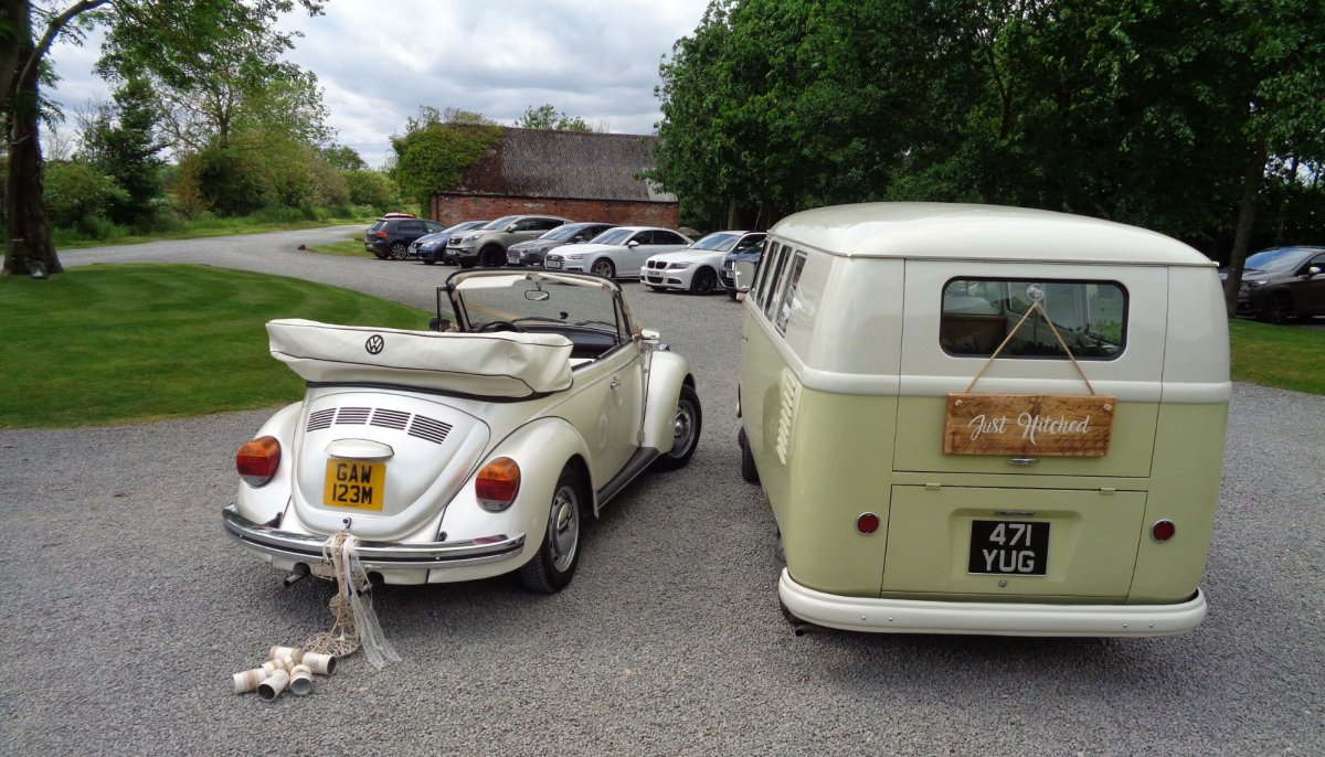 Rear view of ivory vintage VW Beetle cabriolet and VW campervan wedding cars