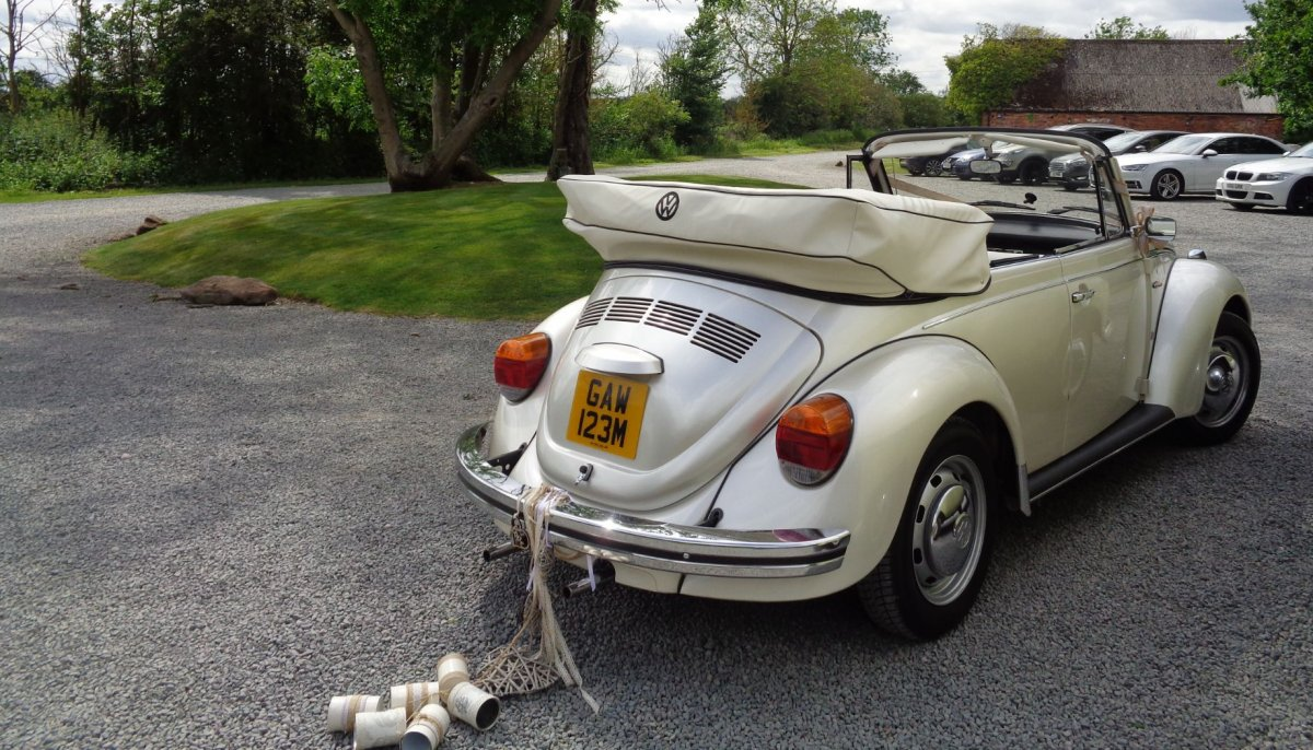 Rear view of an ivory vintage VW Beetle cabriolet wedding car with roof down and some tin cans attached to it's bumper
