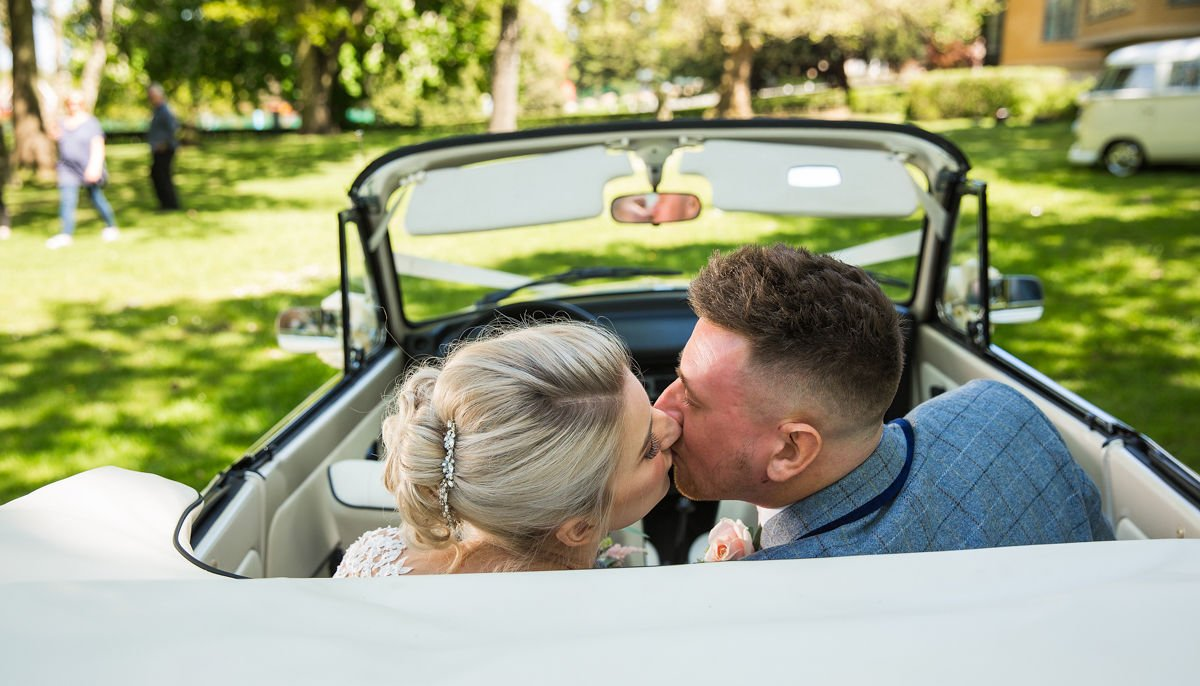 Rear view close up of Bride and Groom kissing sat in the back of an ivory vintage VW Beetle cabriolet wedding car with roof down