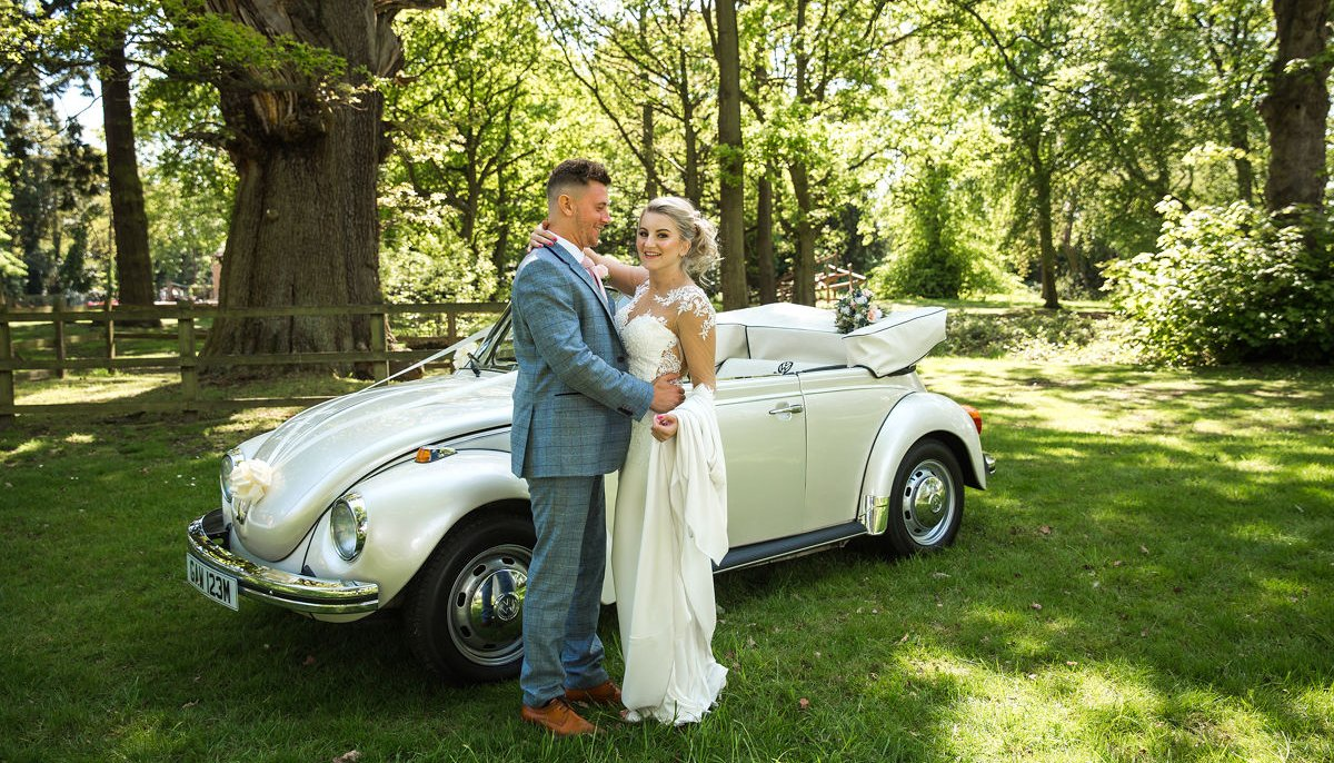 Bride and Groom hugging stood in front of an ivory vintage VW Beetle cabriolet wedding car with roof down, in a park setting