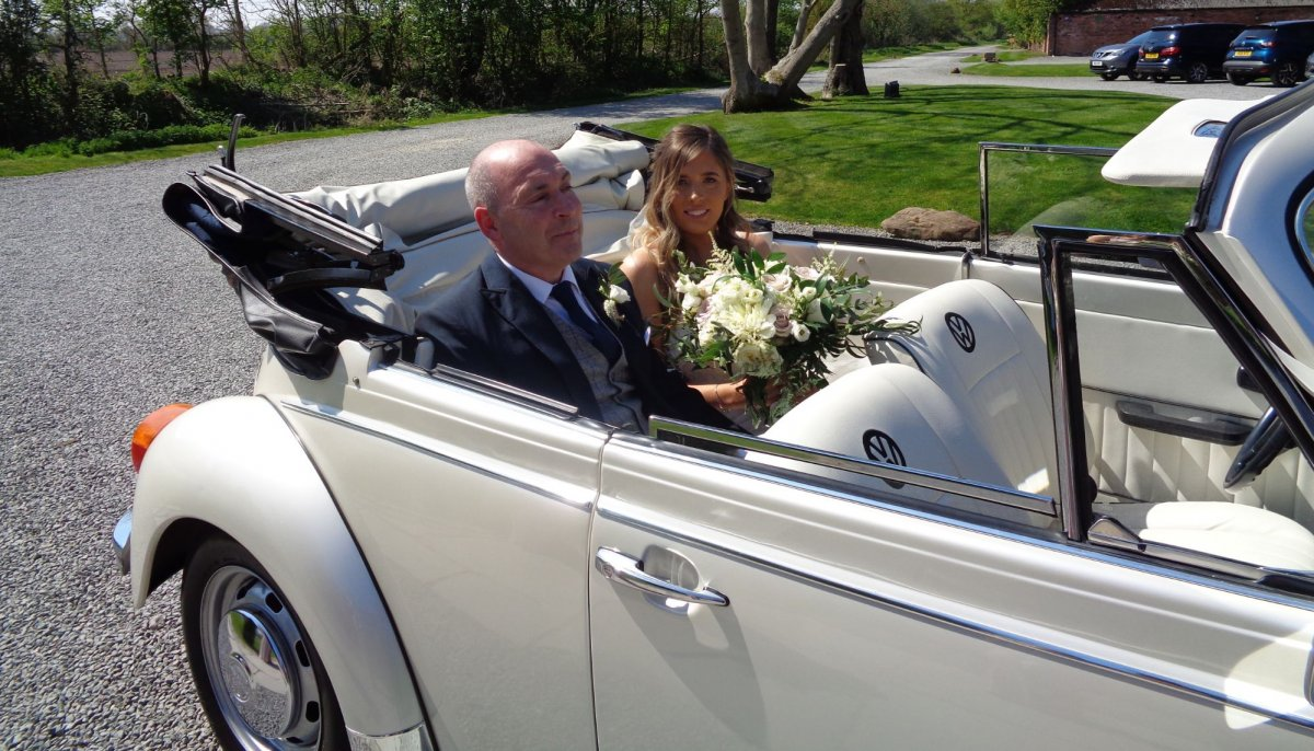 Bride and her father sat in the back of an Ivory vintage VW Beetle cabriolet wedding car with roof down,  outside Shustoke Barn