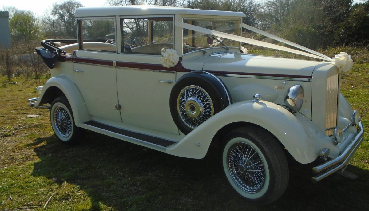 vintage convertible  ivory wedding car with ivory ribbons and bows