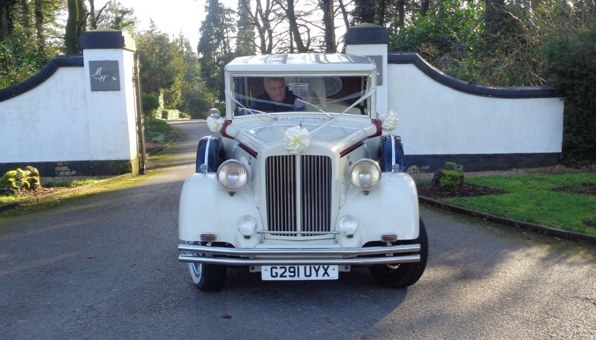 Front view of cream vintage style Regent Landaulet at the entrance to Moxhull Hall hotel