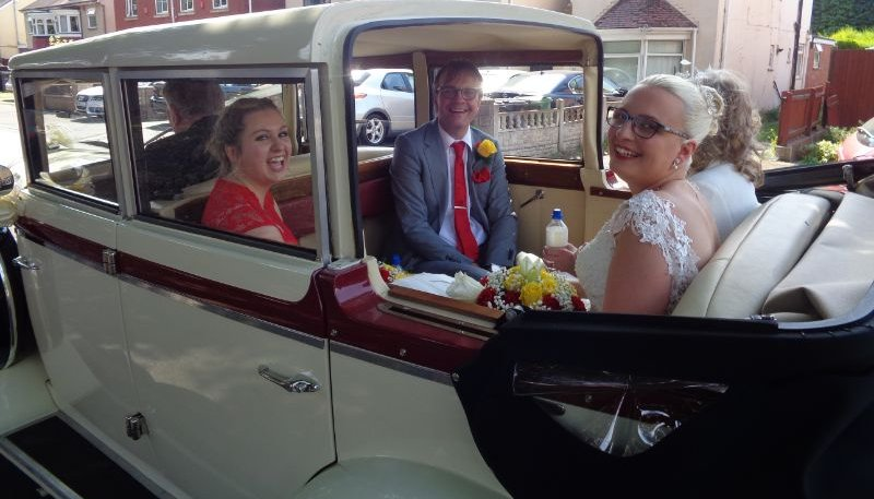 Bride and her family sat in Regent Landaulet vintage style wedding car, with the roof down laughing