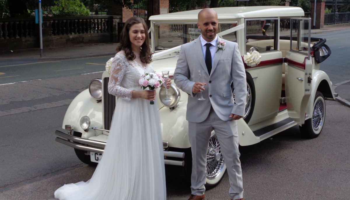 Bride and groom stood in front of an ivory vintage Style Regent Landaulet wedding car with roof down