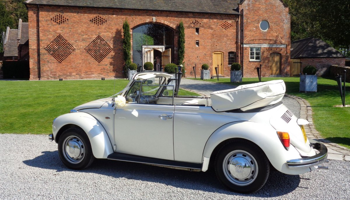 Ivory vintage VW Beetle cabriolet with roof down, parked outside Shustoke Barn