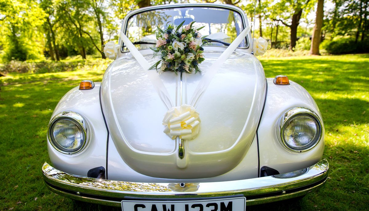 Front view of ivory vintage VW Beetle cabriolet wedding car, with ivory ribbons and bow and a bouquet on it's bonnet