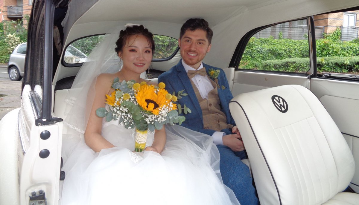 Close up of brdie and groom, sat in the back of an ivory vintage VW Beetle cabriolet wedding car. Bride has a sunflower bouquet in her hands
