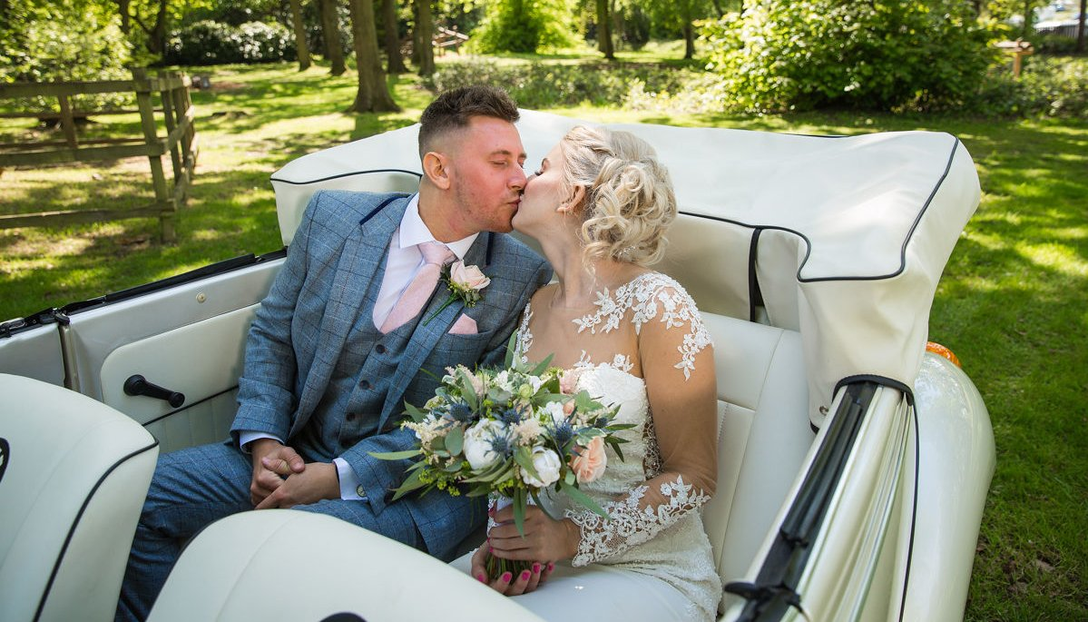 Bride and Groom kissing, sat in the back of an ivory vintage VW Beetle cabriolet with roof down, parked in the grounds of Drayton Manor Hotel